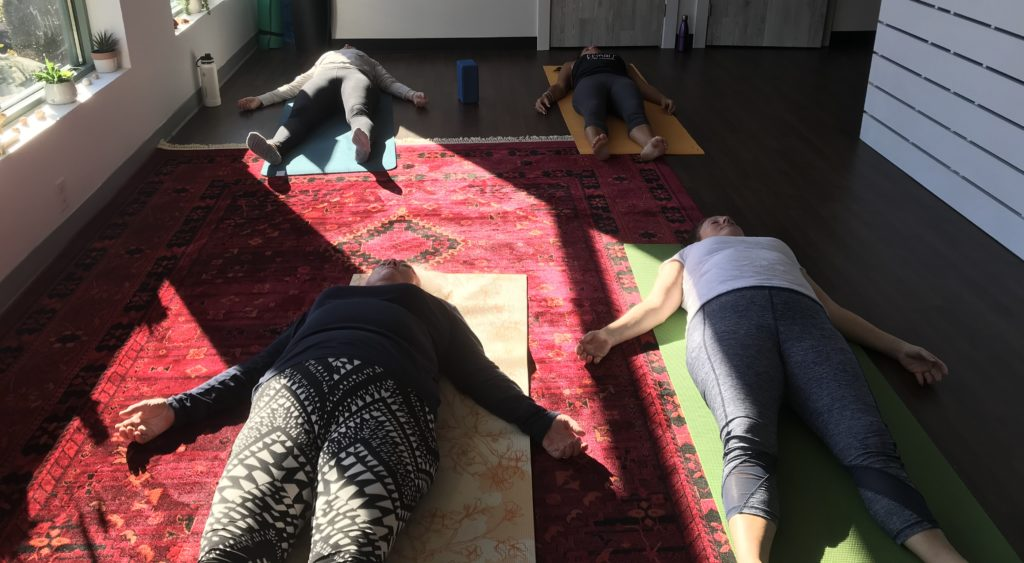 yoga students lying down in corpse pose final meditation savasana